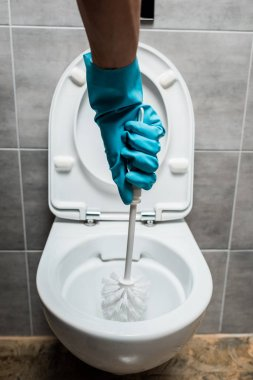 cropped view of cleaner cleaning ceramic toilet bowl with toilet brush in modern restroom with grey tile