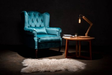 elegant velour blue armchair with pillow near animal skin rug, wooden table and lamp isolated on black
