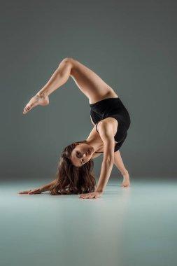 Attractive dancer in black bodysuit dancing contemporary on dark background stock vector