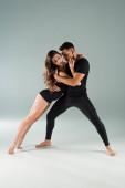 Tänzer mit geschlossenen Augen tanzen zeitgenössisch auf grauem Hintergrund