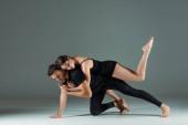 pohledný a atraktivní tanečníci tanec moderní na tmavém pozadí