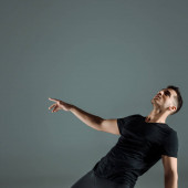 Fotografie handsome dancer in black t-shirt dancing contemporary isolated on grey