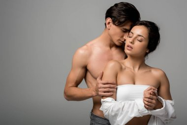 beautiful sensual young couple hugging with closed eyes isolated on grey