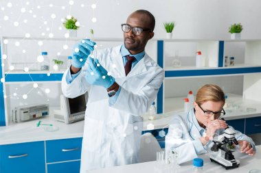 African american biologist holding test tube and standing near illustration, his colleague using microscope stock vector