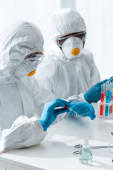 Photo multicultural scientists in protective suits doing dna test in lab