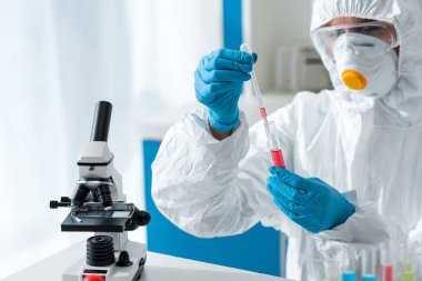 Scientist in protective suit and latex gloves doing dna test stock vector