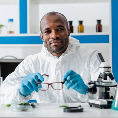 Smiling african american biologist holding glasses and looking at camera stock vector