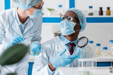 african american biologist in medical mask talking with colleague in lab