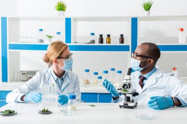 Multicultural biologists in white coats and medical masks talking in lab stock vector