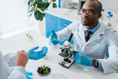 African american biologist sitting at table and looking at his colleague stock vector