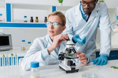 Multicultural biologists in white coats using microscope in lab stock vector