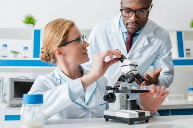 multicultural biologists in glasses looking at microscope in lab
