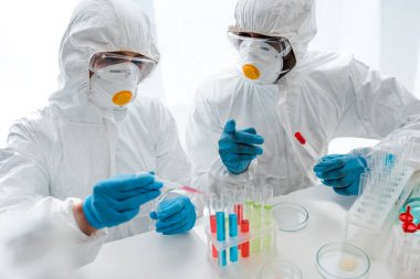 Multicultural scientists in protective suits doing dna test in lab stock vector