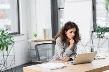pensive account manager sitting at table and looking at laptop