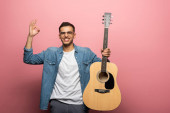 Photo Young man smiling at camera while showing okay sign and holding acoustic guitar on pink background