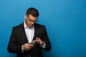 Handsome businessman counting dollar banknotes on blue background