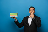 Thoughtful businessman with hand on mouth holding books on blue background