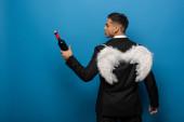 Fényképek Vissza kilátás üzletember fehér szárnyú gazdaság üveg bor a kék háttér