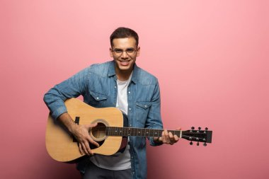 Young man smiling at camera and playing acoustic guitar on pink background