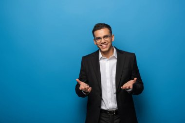 Smiling businessman presenting something and looking at camera on blue background