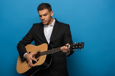 Young businessman playing on acoustic guitar on blue background