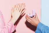 Photo cropped view of man doing marriage proposal to clapping woman on pink and blue background