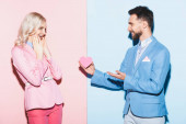 handsome man giving heart-shaped card to shocked woman on pink and blue background