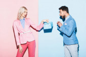 attractive woman giving present to shocked man on pink and blue background