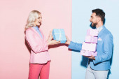 handsome man giving gift to smiling woman on pink and blue background