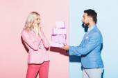 handsome man giving gifts to shocked woman on pink and blue background