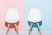 hölzerne und weiße Stühle auf rosa und blauen Hintergrund