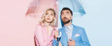 Panoramic shot of shocked woman and handsome man with umbrella looking up on pink and blue background stock vector