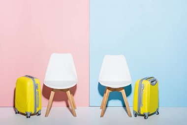 Wooden chairs and travel bags on pink and blue background stock vector