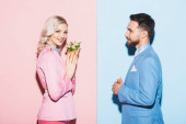 side view of smiling woman with bouquet and handsome man on pink and blue background