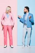 dühös nő és jóképű férfi veszekedés rózsaszín és kék háttér