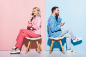 usmívající se žena a hezký muž mluví na chytrých telefonech na růžovém a modrém pozadí