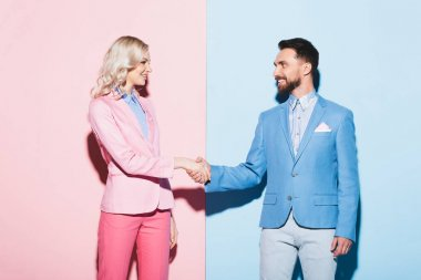 Smiling woman and handsome man shaking hands on pink and blue background stock vector