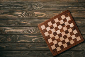 Top view of chessboard on wooden surface