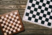 Pohled shora na dva šachovnice na texturovaném dřevěném pozadí