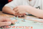 Kyjev, Ukrajina - 15. listopadu 2019: Selektivní zaměření na muže a ženy hrající monopol u stolu