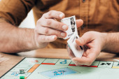 KYIV, UKRAINE - NOVEMBER 15, 2019: Cropped view of man holding explanation cards with monopoly game on table