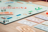 Kyjev, Ukrajina - 15. listopadu 2019: Selektivní zaměření měny hraček a monopolní hry na dřevěný stůl