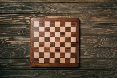 Top view of chessboard on wooden background stock vector