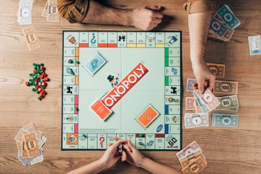 KYIV, UKRAINE - NOVEMBER 15, 2019: Top view of woman with dices and man holding toy currency while playing in monopoly stock vector