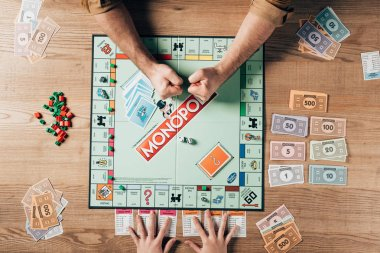 KYIV, UKRAINE - NOVEMBER 15, 2019: Cropped view of man celebrating triumph while playing with woman in monopoly stock vector