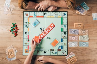 KYIV, UKRAINE - NOVEMBER 15, 2019: Cropped view of woman holding cards while playing with man in monopoly at table stock vector