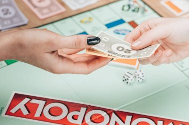 KYIV, UKRAINE - NOVEMBER 15, 2019: Cropped view of women holding toy currency while playing in monopoly stock vector