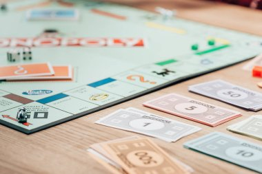 KYIV, UKRAINE - NOVEMBER 15, 2019: Selective focus of toy currency and monopoly game on wooden table stock vector
