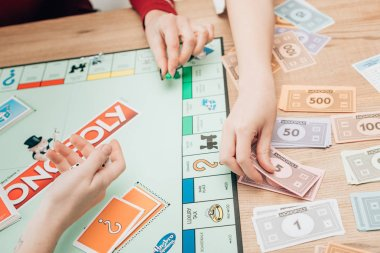 KYIV, UKRAINE - NOVEMBER 15, 2019: Cropped view of women playing monopoly game at table stock vector