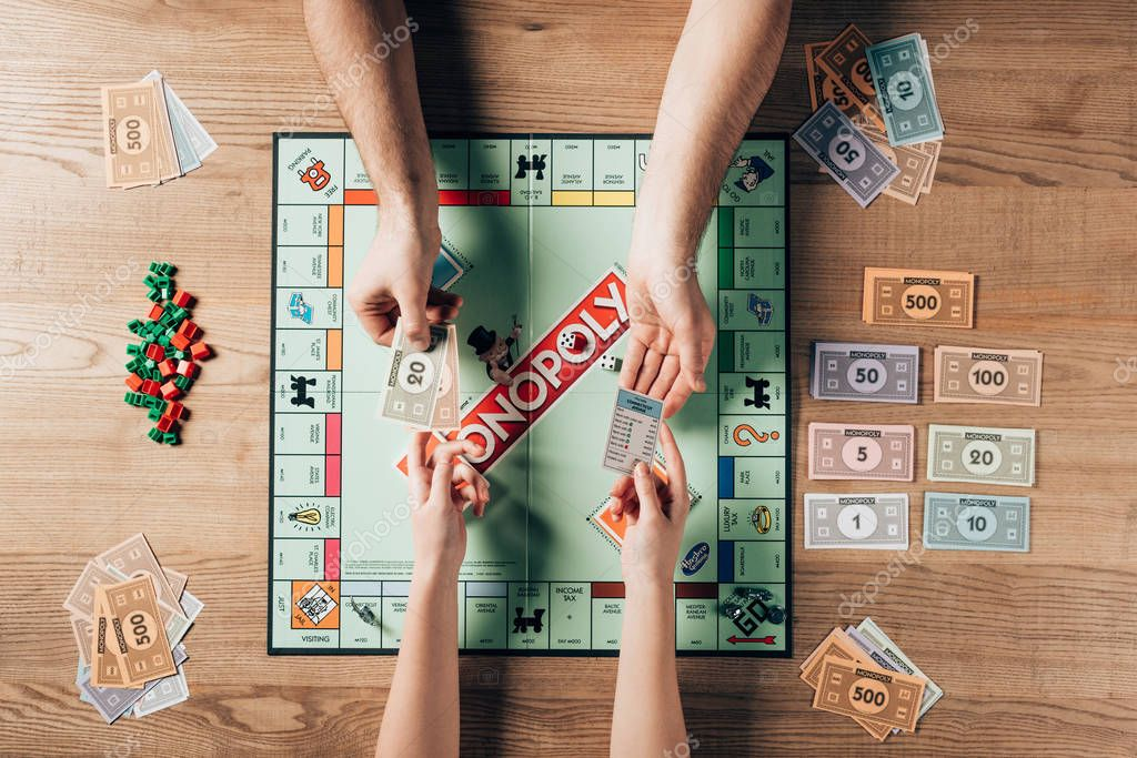 KYIV, UKRAINE - NOVEMBER 15, 2019: Cropped view of man and woman playing monopoly game at table stock vector